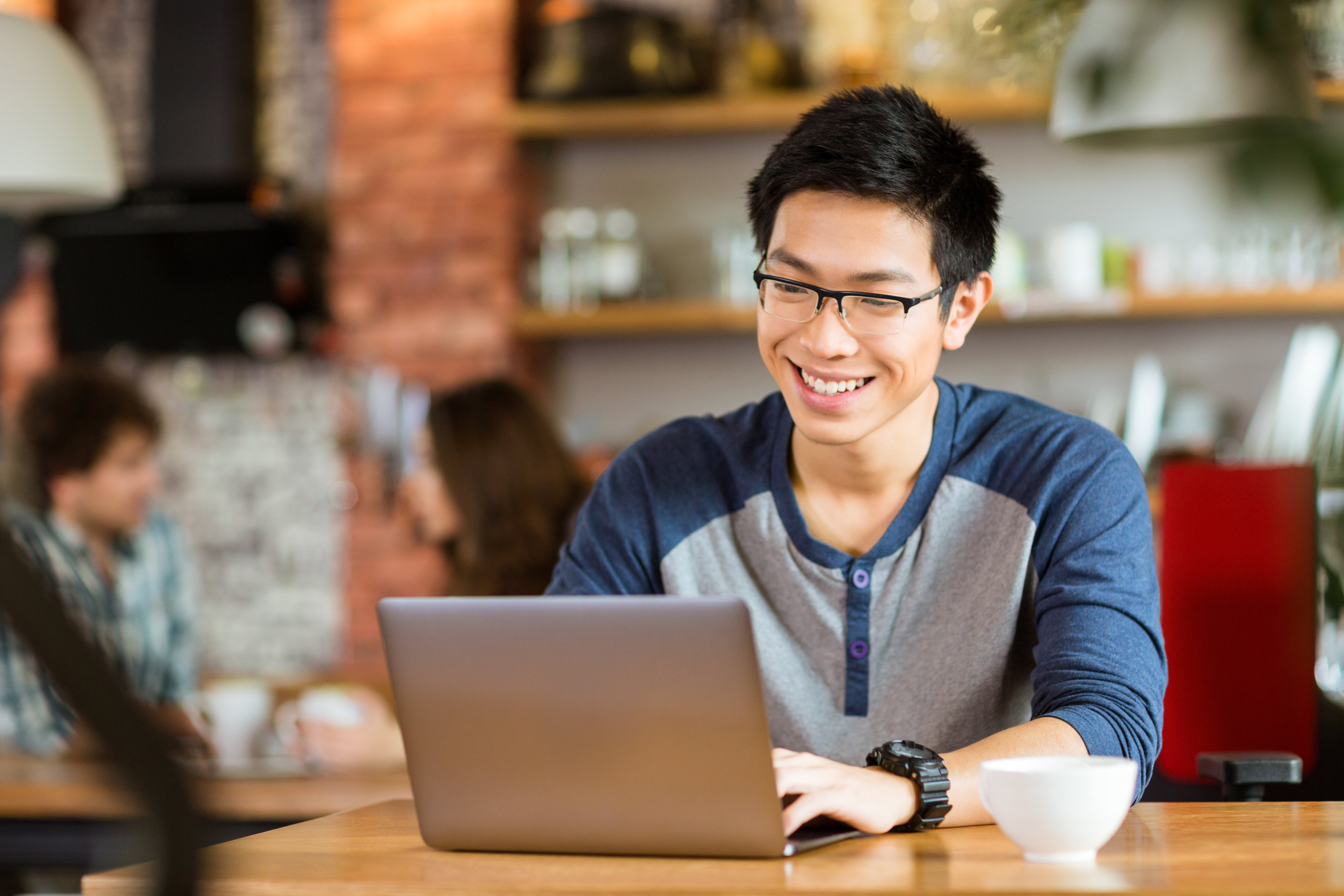 Happy cheerful young asian male in glasses smiling and using laptop in